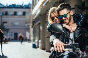 Girl hugging a guy on the motorbike.