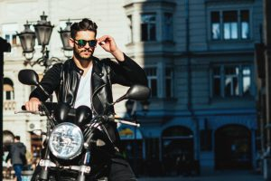 Handsome stylish man posing on a motorcycle in the city.